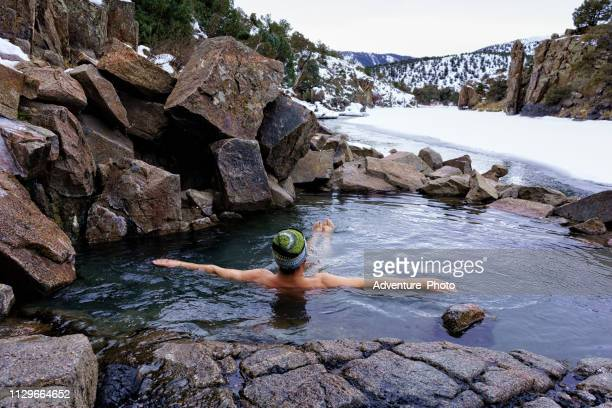 man enjoying relaxing soak in natural hot springs in winter along the colorado river - skinny dipping stock photos and pictures