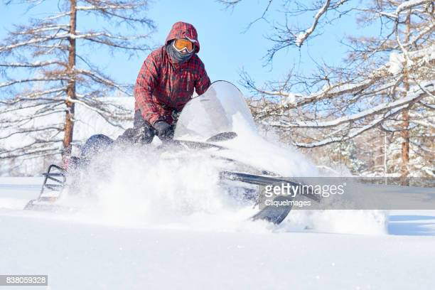 man enjoying snowmobile ride - cliqueimages stock pictures, royalty-free photos & images