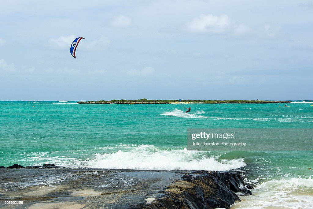 A Man Enjoying Some Recreation Kiteboarding in the Teal Pacific Ocean With Flat Island in the Distance at the Vacation Travel Destination of Kailua Beach on the Island of Oahu