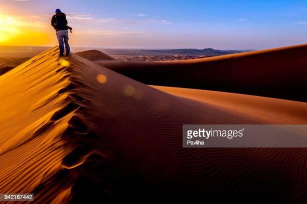 Hombre disfrutando de amanecer en Erg Chebbi dunas, Marruecos, norte de África