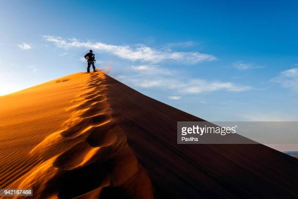 man enjoying sunrise at erg chebbi sand dunes, morocco, north africa - merzouga stock pictures, royalty-free photos & images
