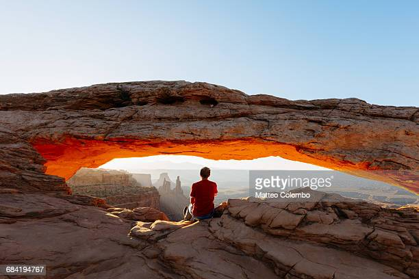 man enjoying sunrise at mesa arch, canyonlands - north america stock pictures, royalty-free photos & images