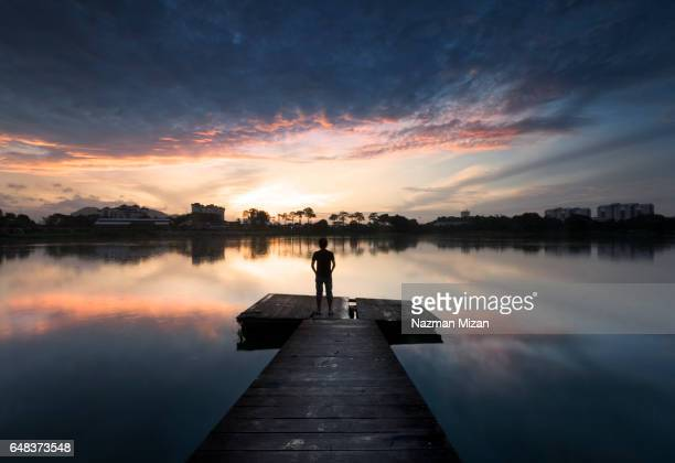 A man enjoying sunrise at the wooden pier. The man travelling to explore the beauty of nature.