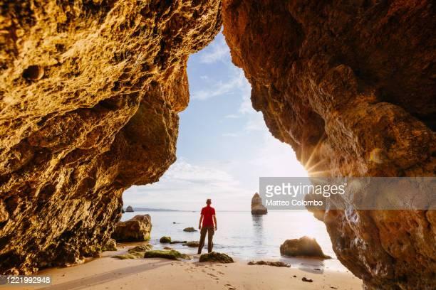 man enjoying sunrise from a cave, algarve, portugal - portugal stockfoto's en -beelden