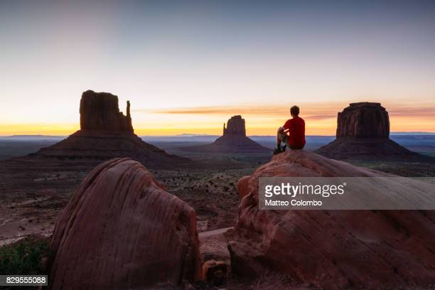 man enjoying sunset over monument valley, usa - monument valley tribal park stock photos and pictures