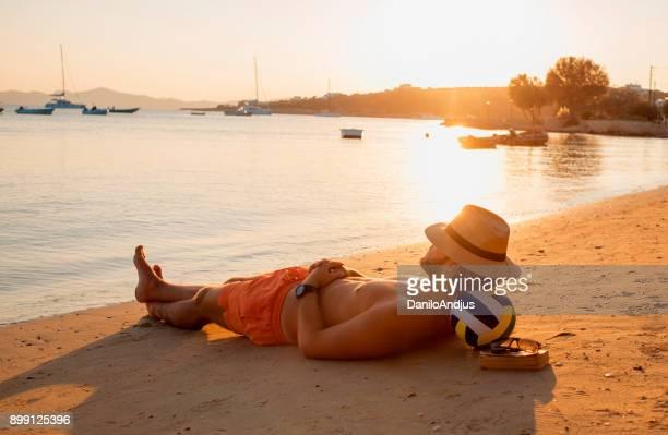 Mann den Sonnenuntergang am Strand genießen