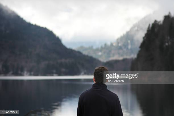 A man enjoying the view at the Snowy European Alps in Alpsee, Schwangau, Bayern, Germany
