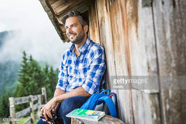 Man enjoying the view from wooden shack, Tirol, Austria
