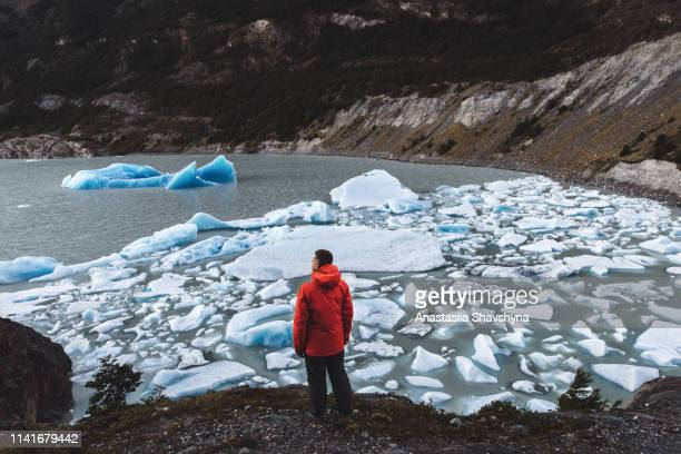 man enjoying the view of icebergs, glacier and mountains at torres del paine - north stock pictures, royalty-free photos & images