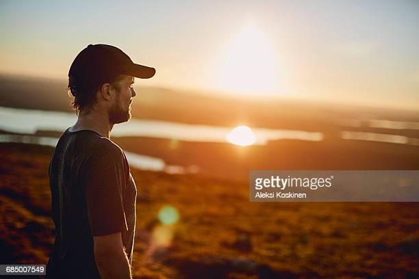 Man enjoying view at sunset, Keimiotunturi, Lapland, Finland