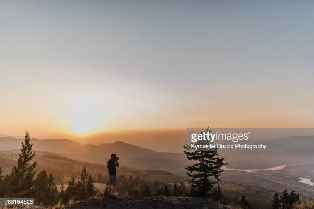 man enjoying view from hill, kamloops, canada - kamloops stock pictures, royalty-free photos & images