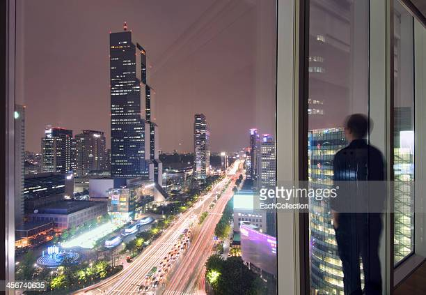 Man enjoying view from window in Seoul
