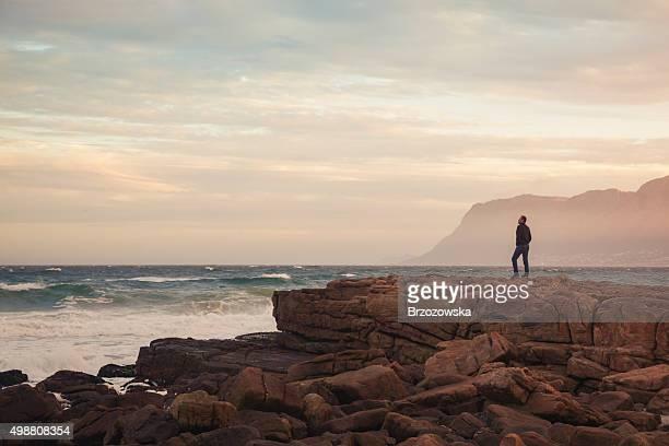 Man enjoying view of wavy ocean during sunset (South Africa)