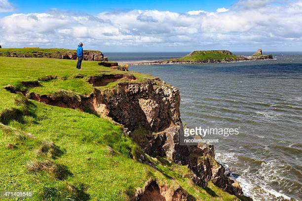 Man enjoying view of Worm's Head, Gower Peninsula, South Wales