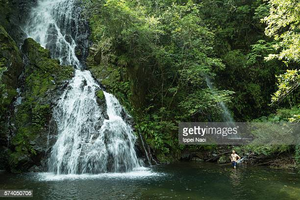 Man enjoying waterfall in rainforest