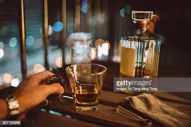 A man enjoying whisky & smoking pipe at night