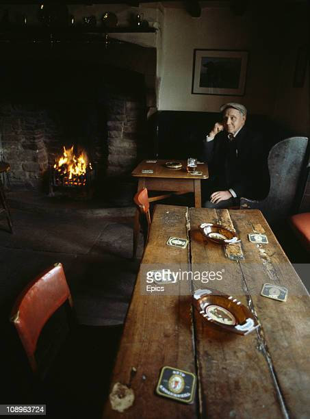 Man enjoys a quiet pint of ale by a real fire in the cosy atmosphere of the Forresters Arms country pub in the rural village of Carlton, North...
