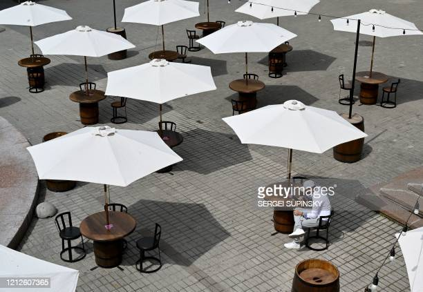 TOPSHOT A man enjoys a snack on the terrace of a cafe in Kiev on May 11 as Ukraine partially lifts some restrictions imposed to curb the spread of...