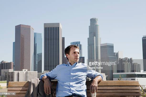 man enjoys a sunny day on a bench in big city