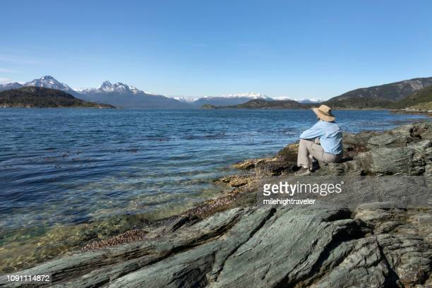 man enjoys beagle channel chilean mountains tierra del fuego national park argentina - milehightraveler stock pictures, royalty-free photos & images