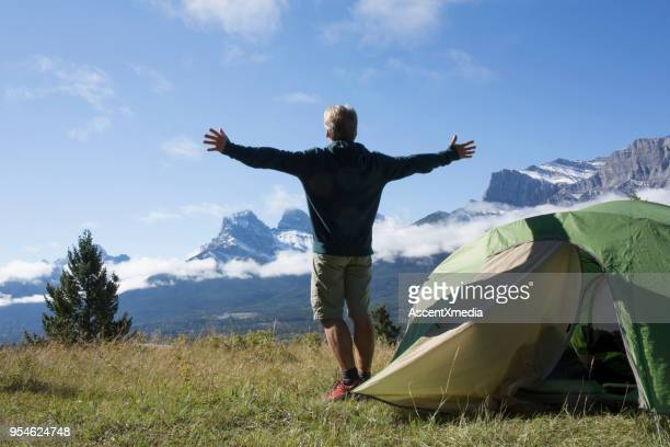 man enjoys camping on a mountain meadow - bow valley stock pictures, royalty-free photos & images