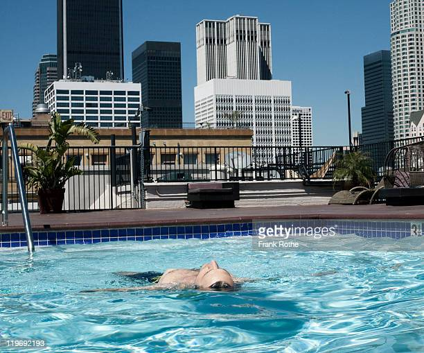 man enjoys his swimming pool in front of a skyline