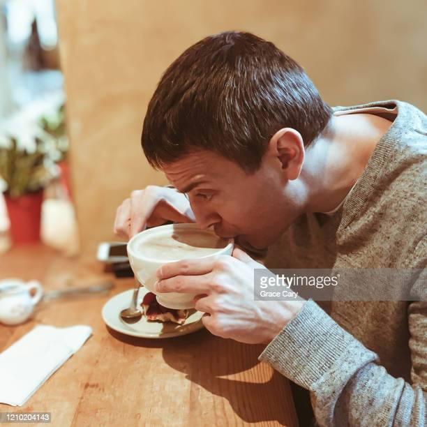 man enjoys hot cocoa at café - cary stockfoto's en -beelden