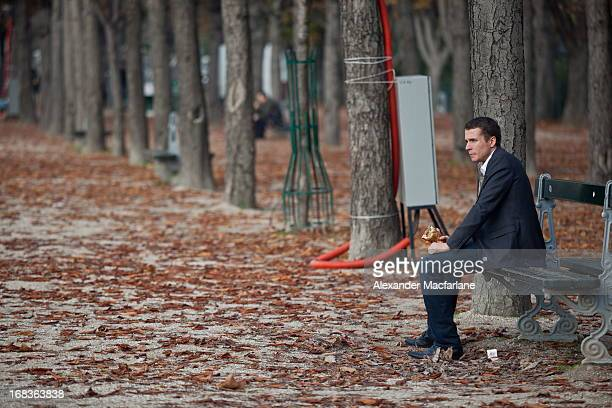 Man enjoys lunch on a park bench in Paris. The autumn leaves have fallen creating an orange blanket.