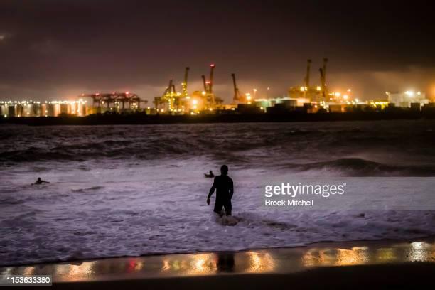 A man enjoys rare waves inside Botany Bay after dark on June 04 2019 in Sydney Australia The Bureau of Meteorology issued a severe weather warning on...