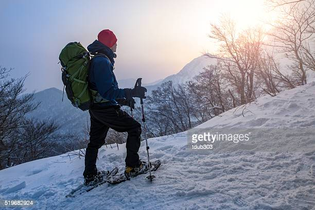 Man enjoys sunrise while snowshoeing through a forest