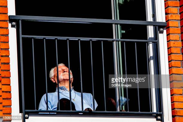A man enjoys the beautiful weather on a balcony of his house The Dutch government ordered closure of public facilities and advised people to stay...