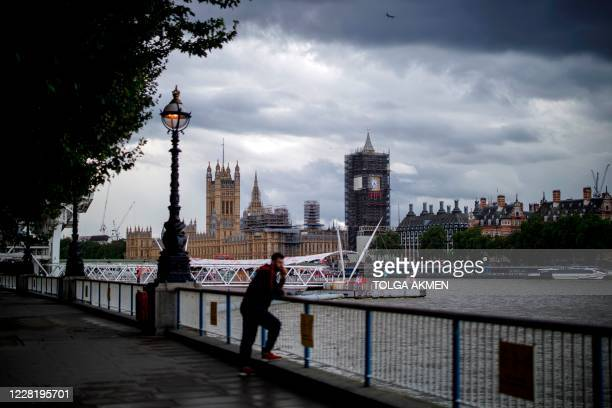 Man enjoys the view from Southbank of the River Thames and Palace of Westminster in central London on August 24, 2020. - For those tourists who do...
