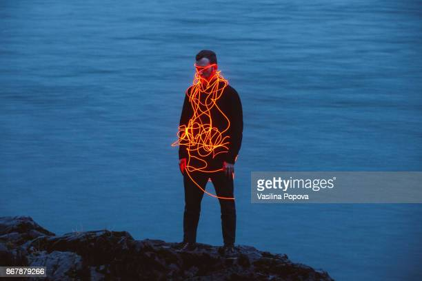 man entangled with neon wires against nature background - modern art stock pictures, royalty-free photos & images