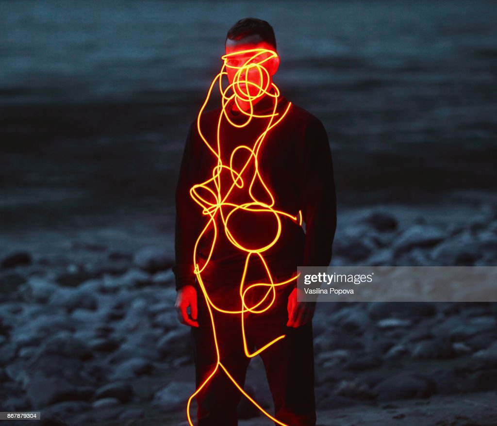Man entangled with neon wires against nature background : Stock Photo