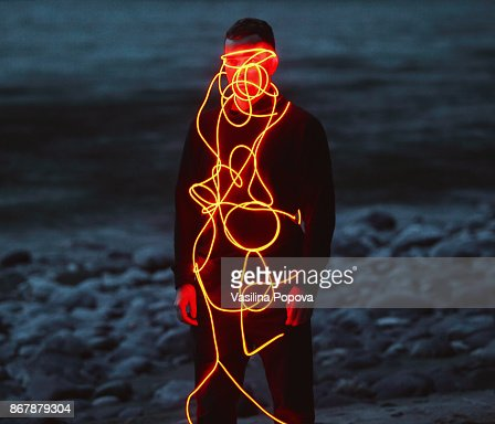 Man entangled with neon wires against nature background