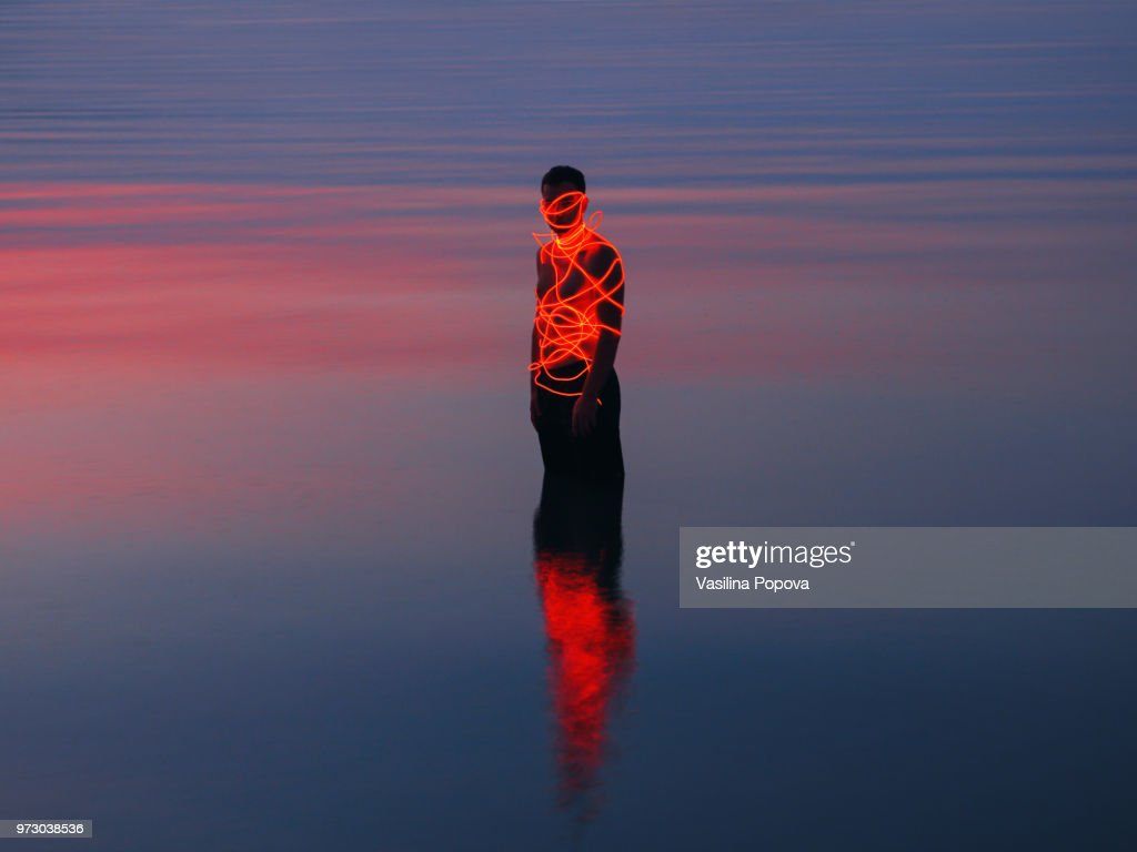 Man entangled with neon wires against sea background : Foto de stock