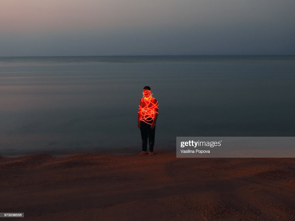 Man entangled with neon wires against sea background : Stock-Foto