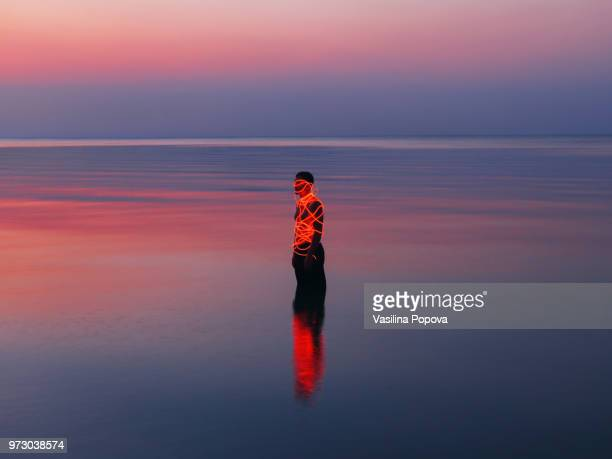 Man entangled with neon wires against sea background