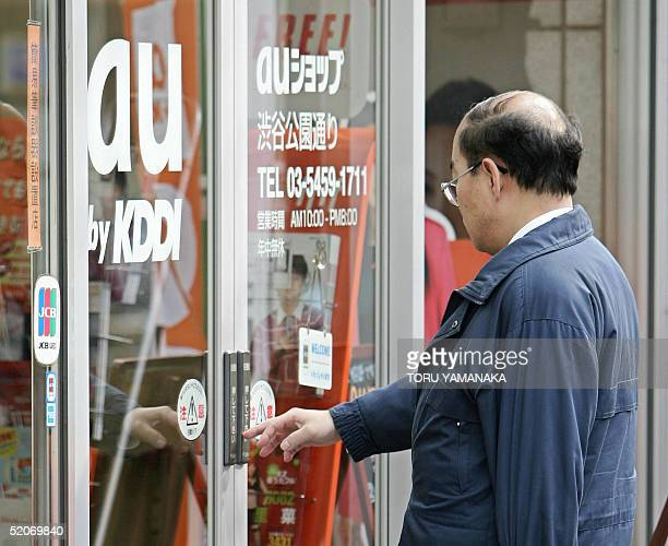 A man enter a mobile phone shop of 'au' mobile service brand of Japan's number two telecoms operator KDDI in Tokyo 27 January 2005 KDDI's net profit...