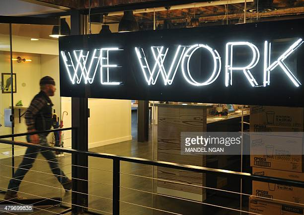 A man enter the doors of the 'WeWork' cooperative coworking space on March 13 2013 in Washington DC In a large warehousetype office in Washington...