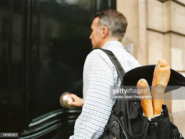 Man entering a building with baguettes in his backpack