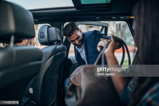 hombre entrando en un paseo compartiendo coche - entrando fotografías e imágenes de stock