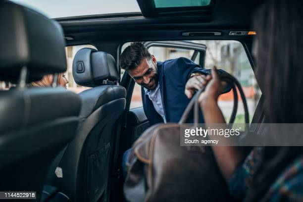 man entering a ride sharing car - taxi foto e immagini stock
