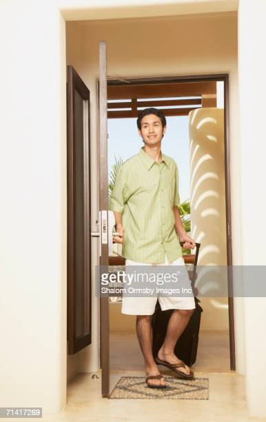 Man entering hotel room with suitcase