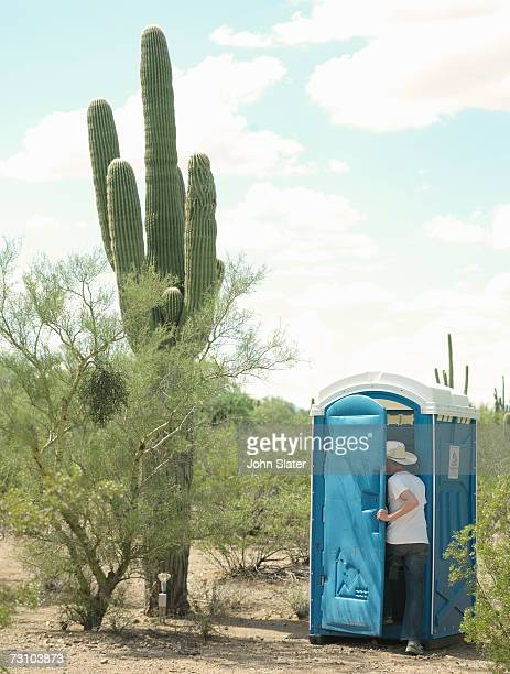 man entering portable toilet in desert, rear view - portable toilet stock photos and pictures