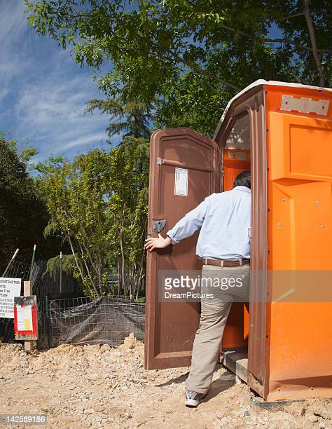 man entering portable toilet - portable toilet stock photos and pictures
