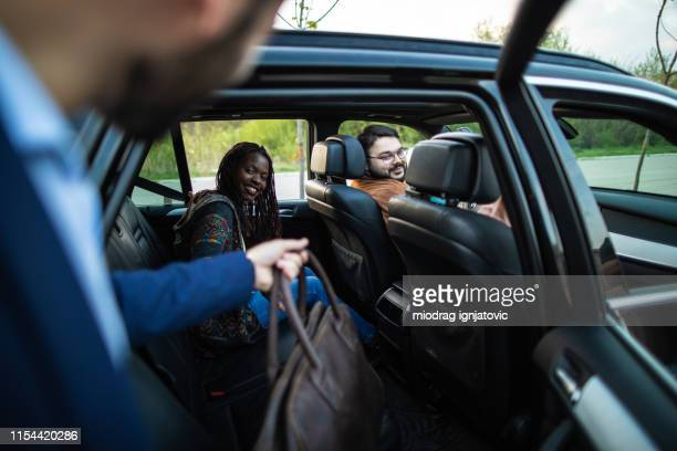 man entering ride sharing car - car pooling stock photos and pictures