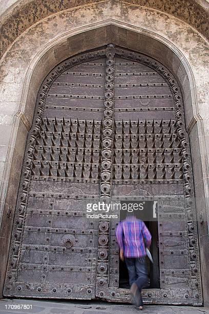 A man entering Shaniwarwada through the iron gate Pune Maharashtra India