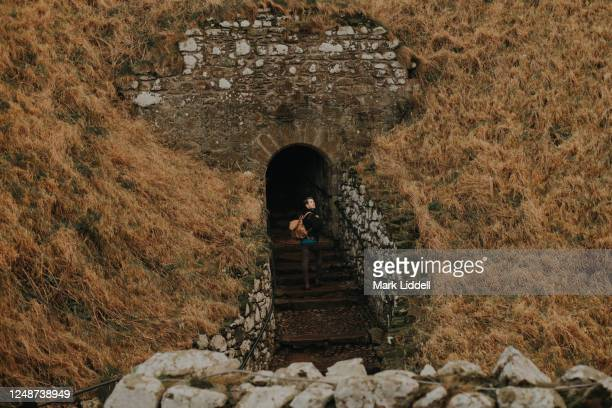 man entering the ruins of dunnottar castle, scotland - castle stock pictures, royalty-free photos & images