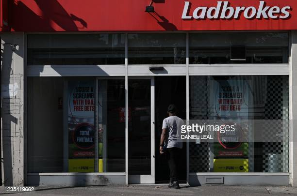 Man enters a Ladbrokes betting shop in east London on September 22, 2021. - UK gambling giant Entain said on Wednesday it had received a takeover bid...